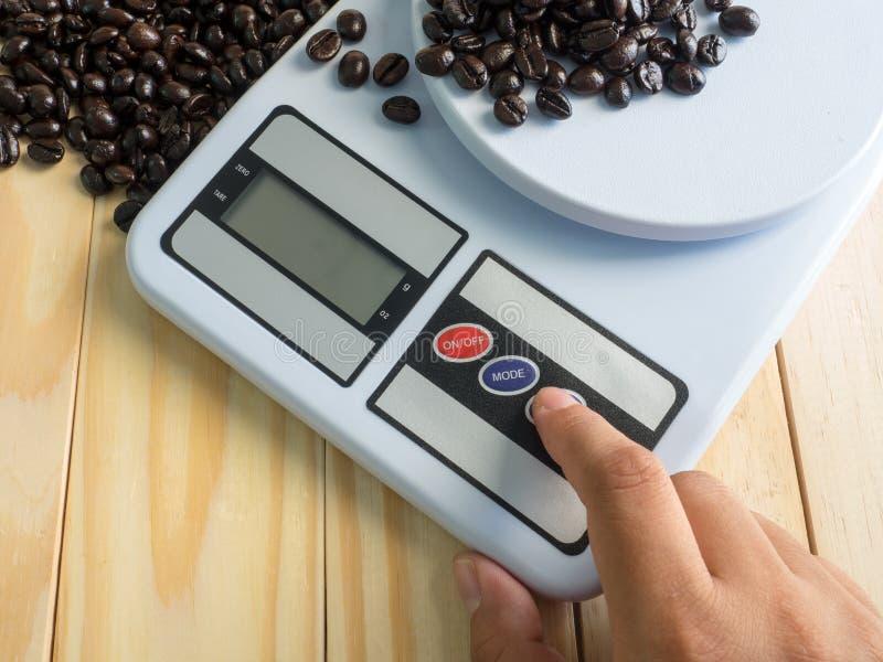 Remettez la presse sur l'appareil de mesure numérique et les grains de café image stock