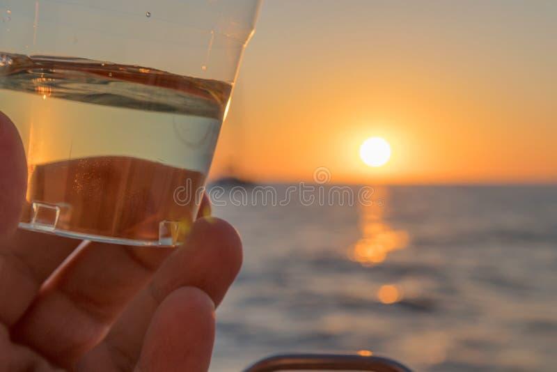Remettez la saisie en verre de vin blanc avec le coucher du soleil et la vue d'océan images libres de droits