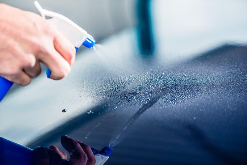 Remettez la substance de nettoyage de pulvérisation sur la surface d'une voiture bleue photos stock
