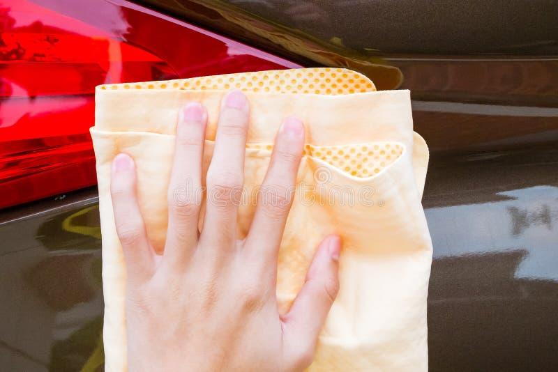 Remettez la voiture de lavage avec la serviette jaune de microfiber de chamois images stock