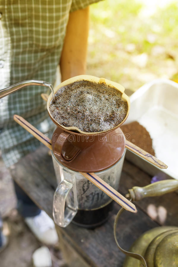 Remettez le café d'égouttement, l'eau de versement de barman sur le marc de café avec f image stock