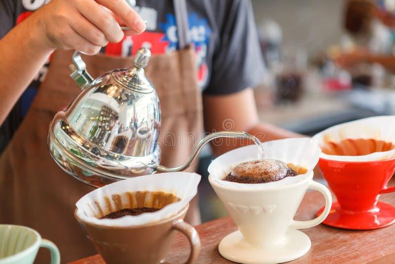 Remettez le café d'égouttement, l'eau de versement de barman sur le marc de café avec le fi photos libres de droits