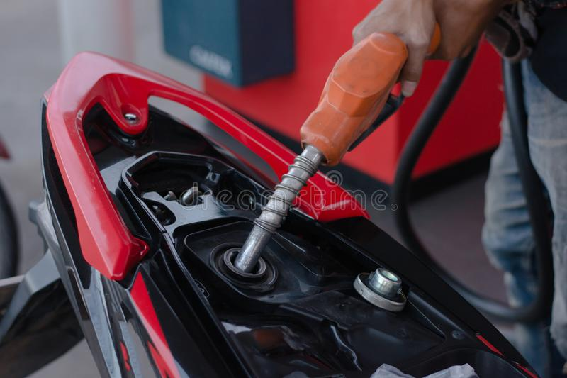 Remettez le gicleur d'essence dans le versement à la moto à la station service image libre de droits