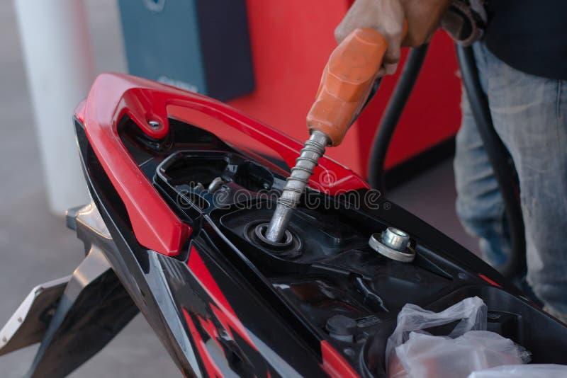 Remettez le gicleur d'essence dans le versement à la moto à la station service photographie stock