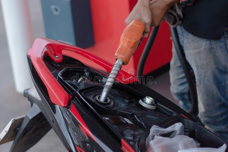 Remettez le gicleur d'essence dans le versement à la moto à la station service photos stock