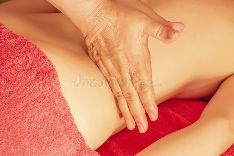 Remettez le massage la fille se trouve sur le divan et fait son massage de mains photo libre de droits
