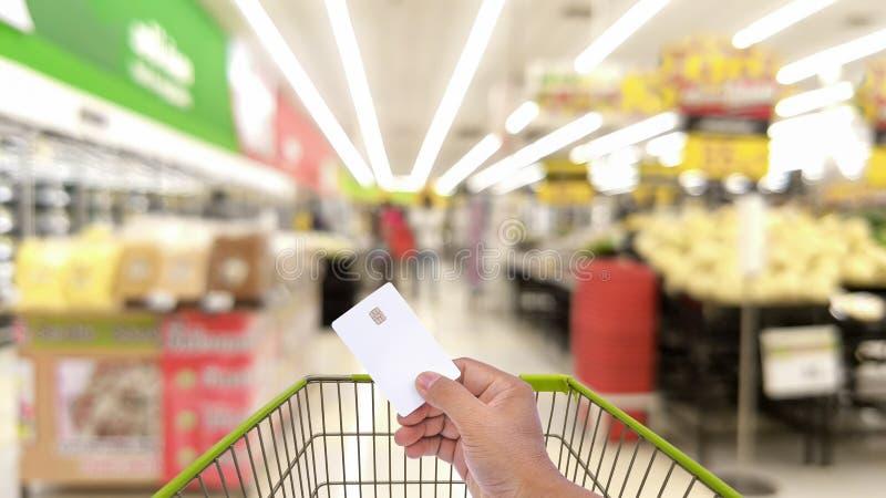 Remettez les hommes tenant la carte de crédit en blanc, carte de distributeur bancaire avec le caddie photo libre de droits