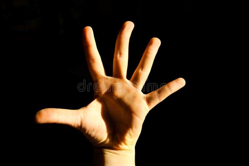 Remettez montrer à haute cinq doigts sur le fond noir photos stock