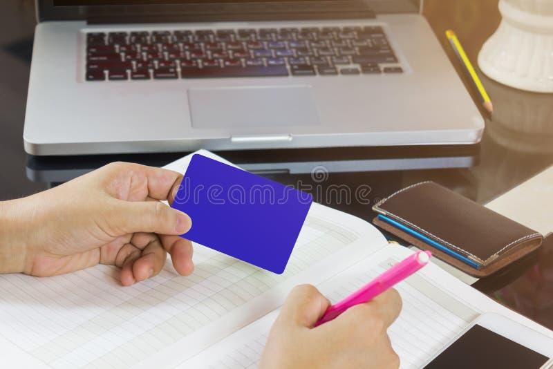 Remettez prennent la carte vierge et le stylo notant sur le carnet vide ou image libre de droits