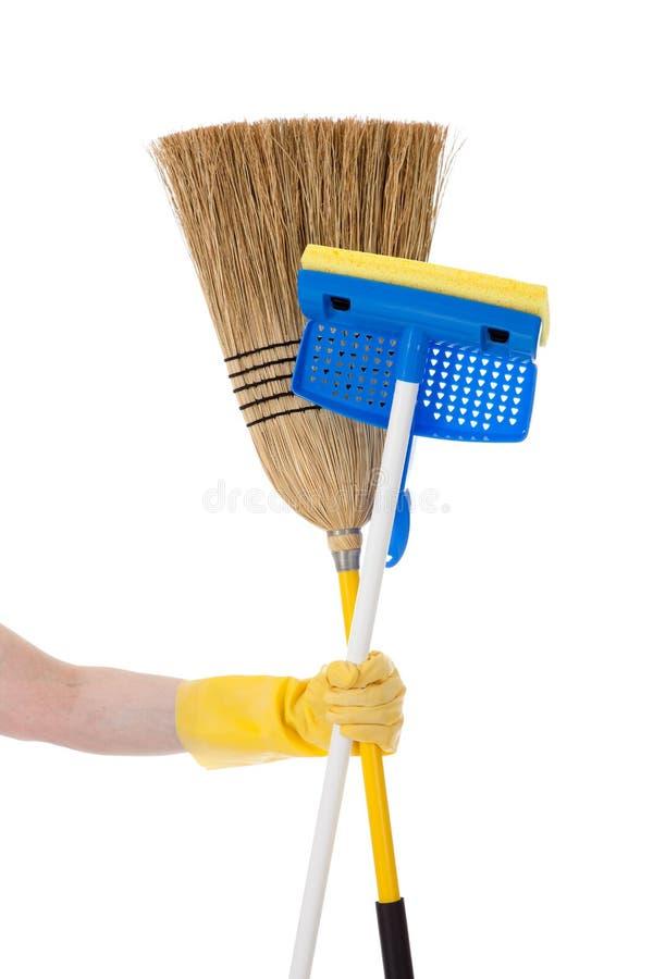 Remettez retenir une lavette et un balai - travaux du ménage images stock