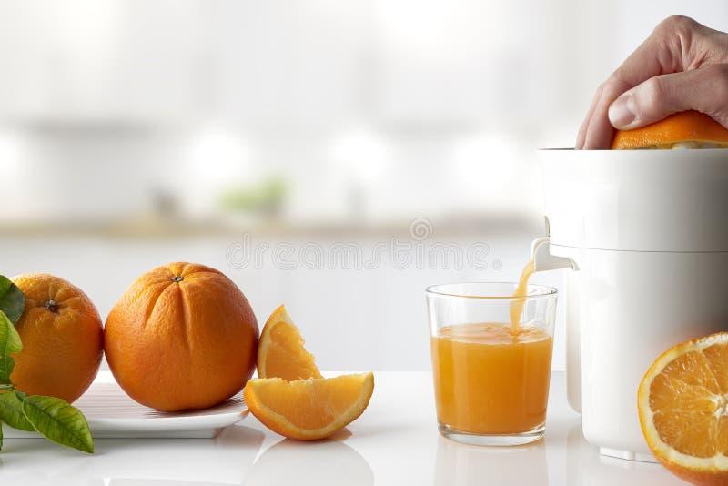Remettez serrer une orange sur un compositi horizontal de table de cuisine photo libre de droits