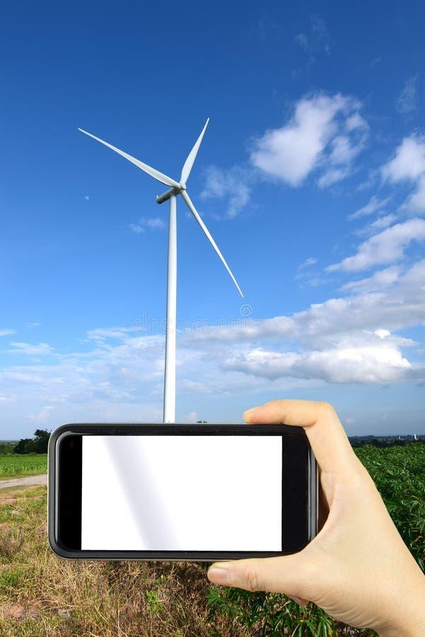 remettez shoting par le téléphone intelligent avec le windmi de turbines de vent de fond image libre de droits