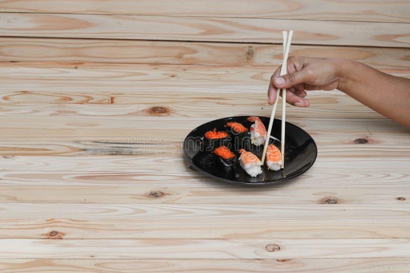 Remettez tenir des baguettes de sushi sur un fond en bois de table de plat noir image stock