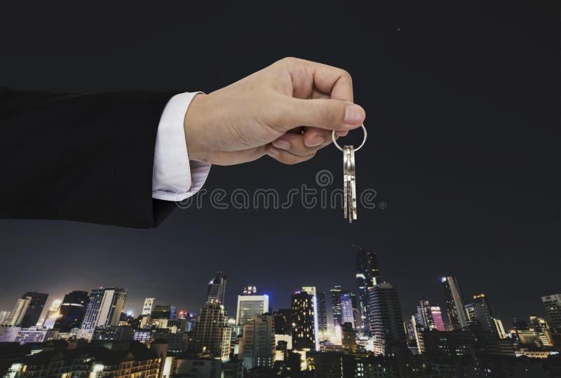 Remettez tenir des clés avec le fond de ville, les immobiliers et le concept de propriété image libre de droits