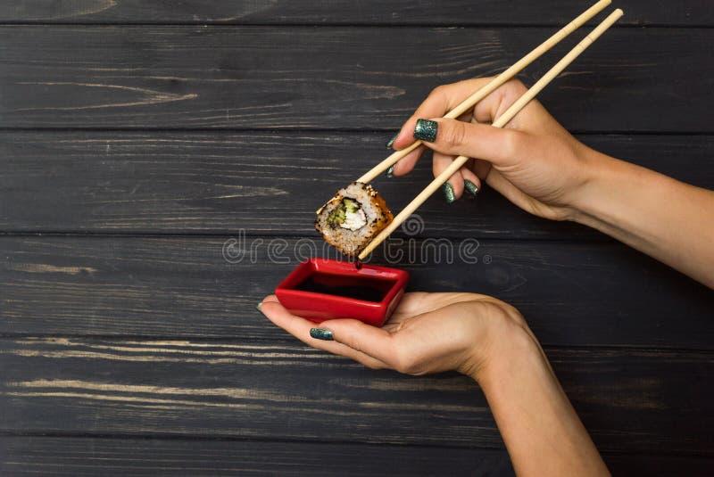 Remettez tenir des sushi avec des baguettes sur un fond en bois noir photo stock