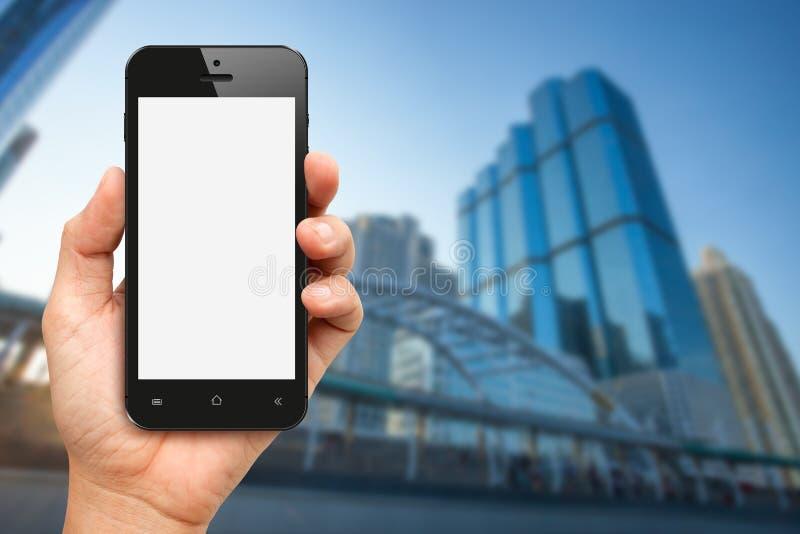 Remettez tenir l'écran vide téléphone intelligent avec le bureau buiding photos stock