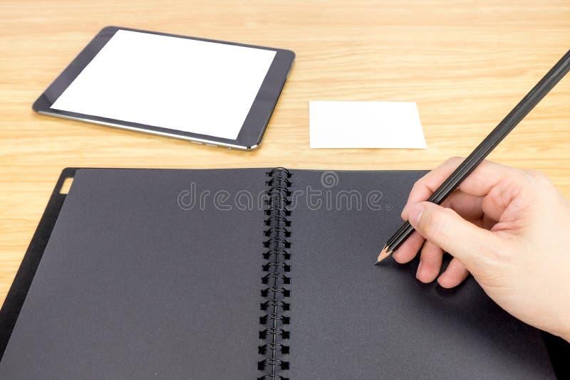 Remettez tenir l'écriture de crayon sur le livre noir vide avec la table et le b photos libres de droits
