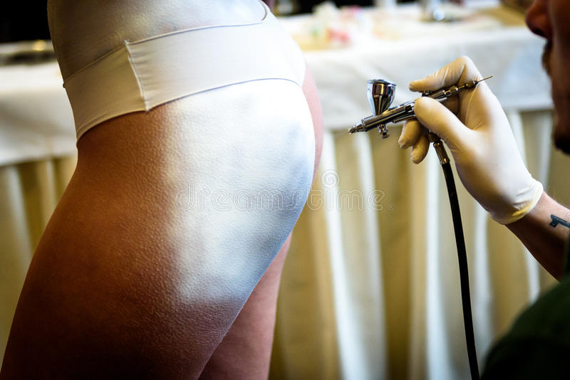 Remettez tenir l'aérographe dans le corps de femme de peinture de corps photo libre de droits