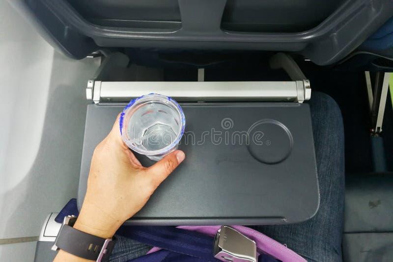 Remettez tenir l'eau minérale jetable sur la table dans l'avion d'air photographie stock libre de droits