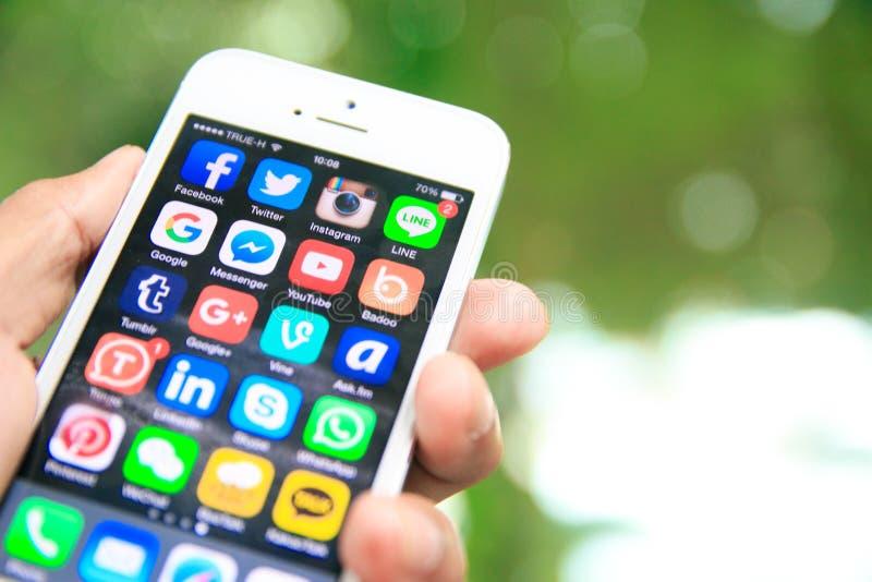 Remettez tenir l'iPhone avec des applications sociales de media sur l'écran photos stock