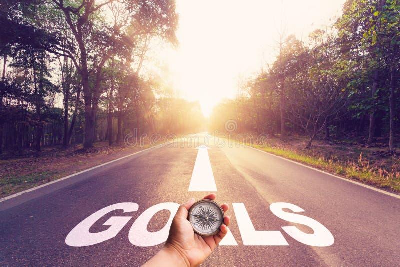 Remettez tenir la boussole sur la route goudronnée vide et le concept de buts image stock