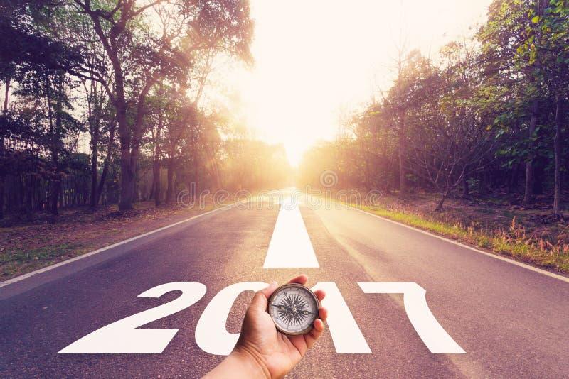 Remettez tenir la boussole sur la route goudronnée vide et le concept 2017 de nouvelle année images stock