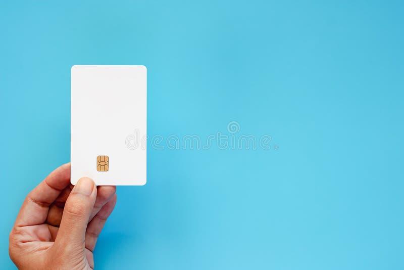 Remettez tenir la carte à puce de crédit en blanc sur le fond bleu images stock