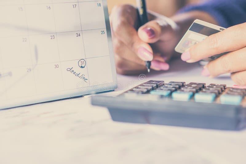 Remettez tenir la carte de crédit calculant ses dépenses mensuelles avec le calendrier de date-butoir images stock