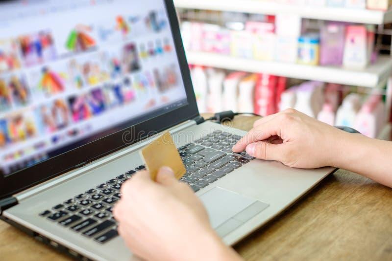 Remettez tenir la carte de crédit et employer l'onlin d'achats de paiement d'ordinateur portable photographie stock