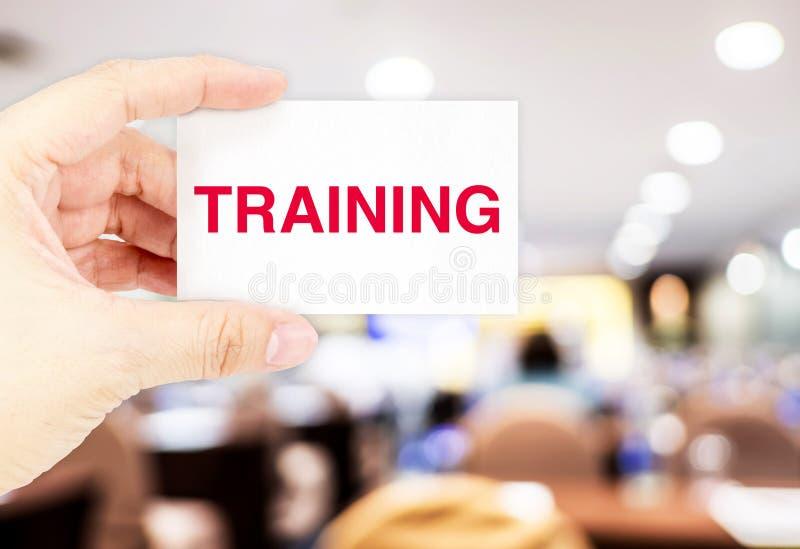 Remettez tenir la carte de visite professionnelle de visite avec le mot de formation lors du séminaire ha de tache floue images stock