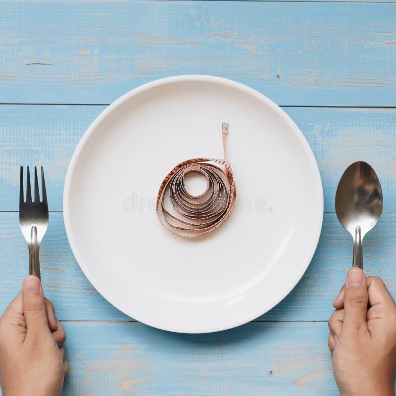 Remettez tenir la cuillère et la fourchette au-dessus du plat blanc avec la bande de mesure rose sur la table en bois bleue de co photographie stock