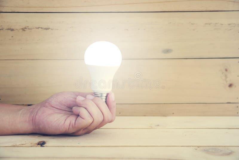 Remettez tenir la lampe de LED avec l'ampoule sur le fond en bois image stock