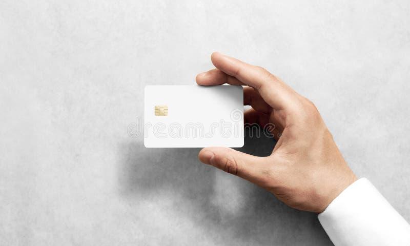 Remettez tenir la maquette blanche vide de carte de crédit avec les coins arrondis photographie stock