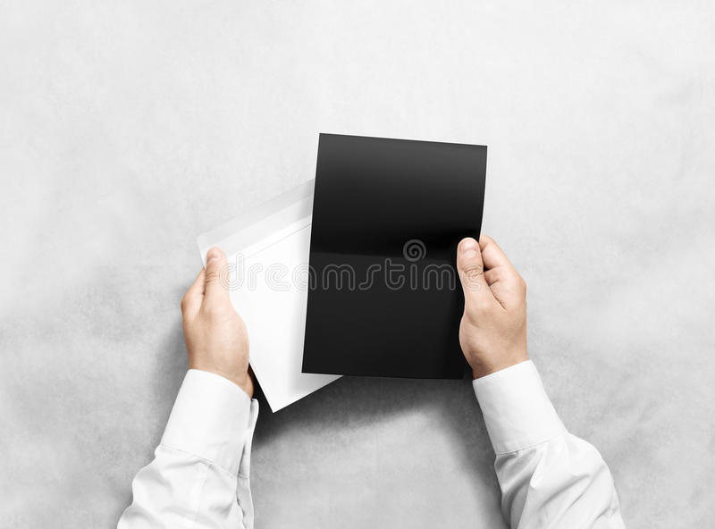 Remettez tenir la maquette d'enveloppe vide et de lettre noire, d'isolement image stock