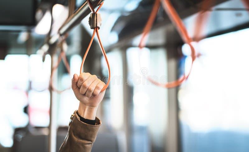 Remettez tenir la poignée dans le tram, le train, l'autobus ou le souterrain images libres de droits