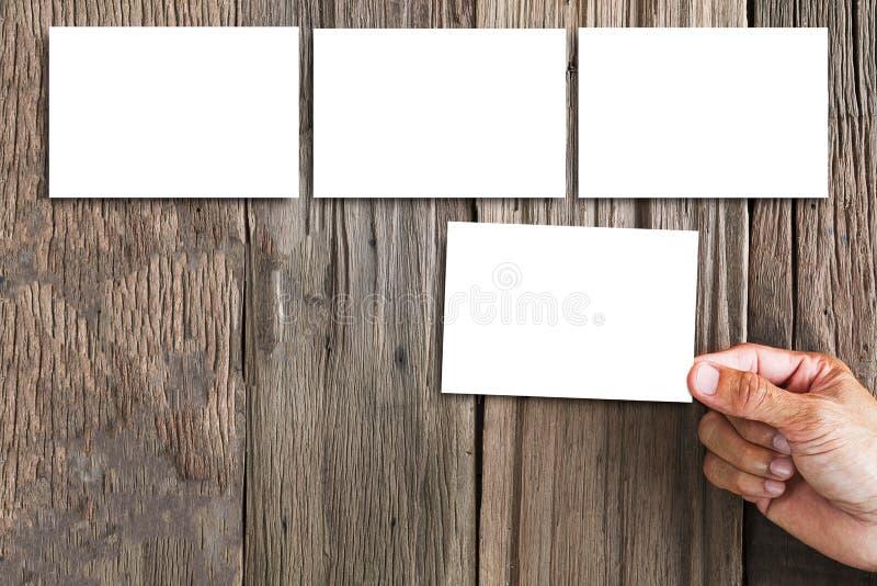 Remettez tenir le cadre blanc de photo et quelques cadres de photo de blanc sur le fond en bois grunge de vintage image libre de droits