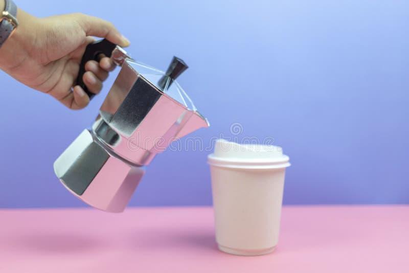 Remettez tenir le café se renversant de fabricant d'expresso dans la tasse de papier image libre de droits