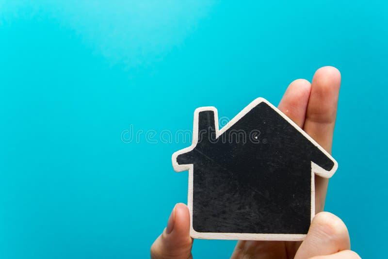 Remettez tenir le chiffre de maison de livre blanc sur le fond bleu Concept 6 d'immeubles Copiez la vue supérieure de l'espace photos stock