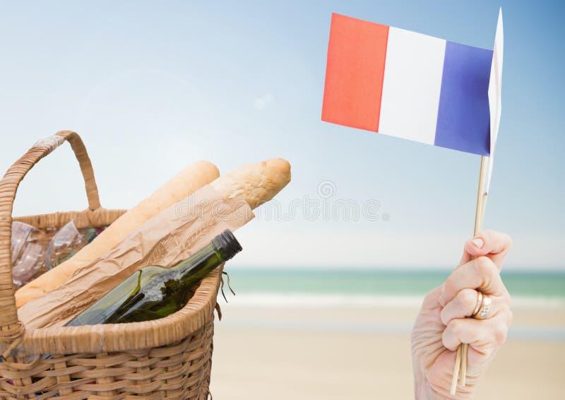 Remettez tenir le drapeau français avec les baguettes et le vin sur la plage photo libre de droits