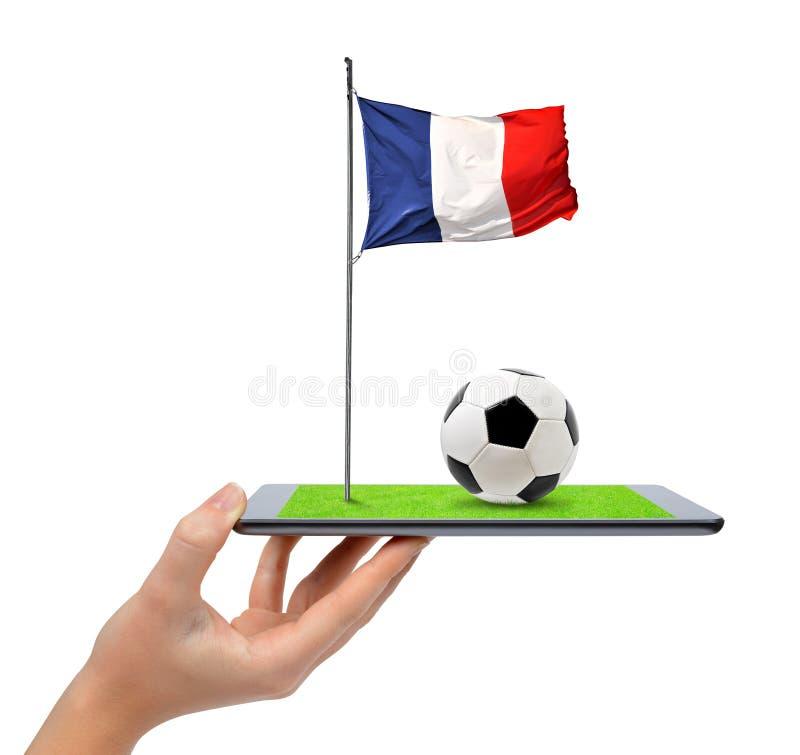 Remettez tenir le PC numérique de comprimé avec du ballon de football et le drapeau de Français images stock