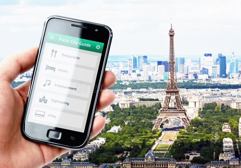 Remettez tenir le smartphone avec le guide de ville à Paris image stock