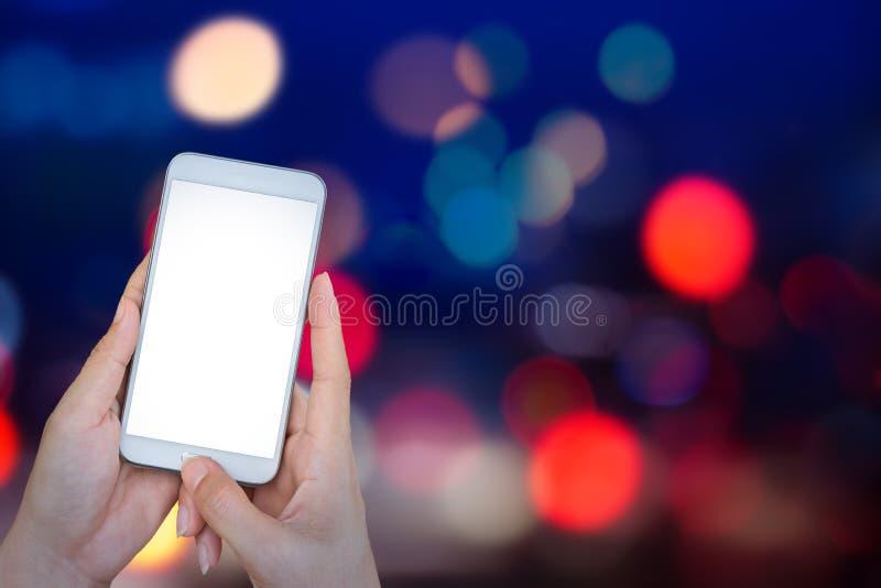 Remettez tenir le téléphone intelligent avec le bokeh de lumières de résumé sur le CCB noir photographie stock libre de droits