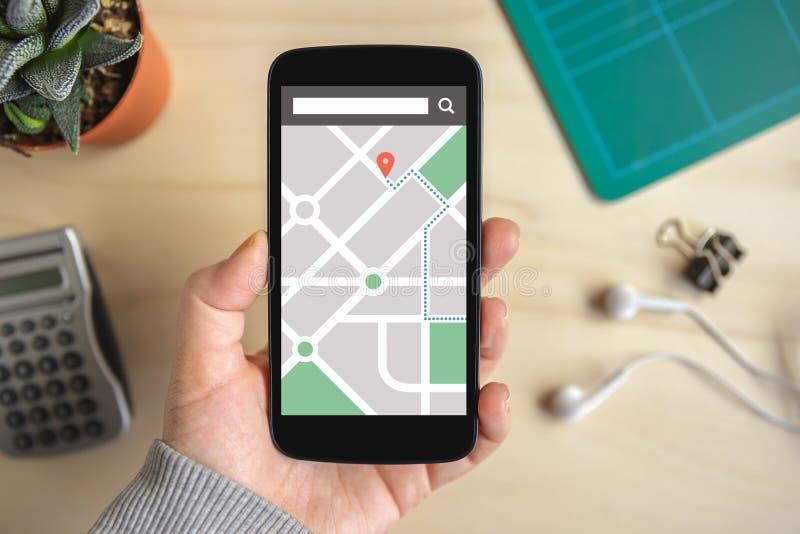 Remettez tenir le téléphone intelligent avec l'application de navigation de généralistes de carte dessus images stock