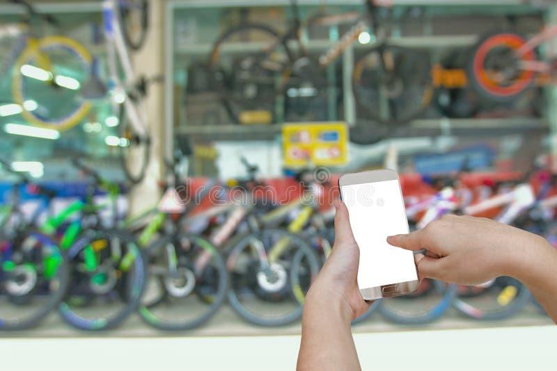Remettez tenir le téléphone intelligent mobile avec le CCB trouble de bicyclette de salle d'exposition photos libres de droits