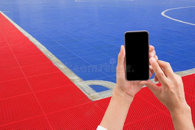 Remettez tenir le téléphone intelligent mobile avec l'écran noir, image de tache floue de photographie stock libre de droits