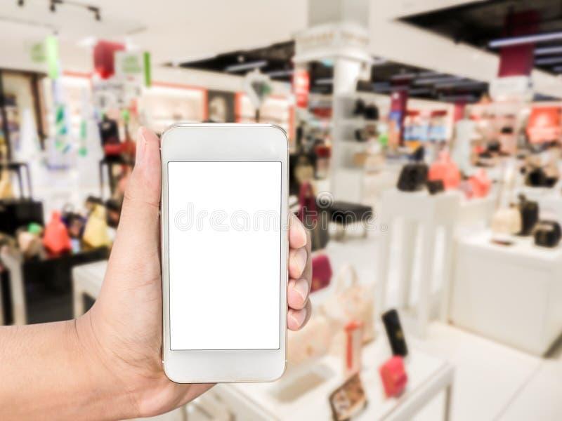 Remettez tenir le téléphone intelligent mobile sur des chaussures et des sacs de mode photographie stock libre de droits
