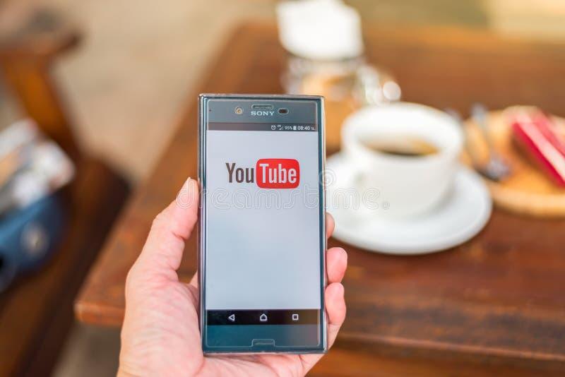 Remettez tenir le téléphone portable avec le logo de Youtube dans le café photos libres de droits