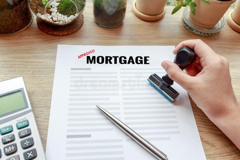 Remettez tenir le tampon en caoutchouc avec le document, le stylo et le calcul d'hypothèque image libre de droits