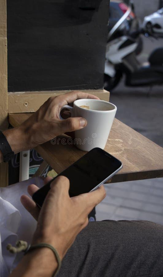 Remettez tenir un mobile et un café sur une terrasse d'une barre photo libre de droits