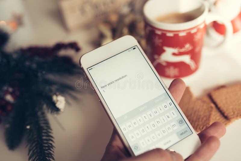 Remettez tenir un smartphone et écrire des résolutions de nouvelle année photos libres de droits